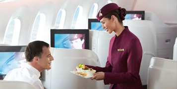 Cabin crew serving a meal to a passenger.