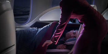 Cabin crew covering a sleeping passenger in business class.
