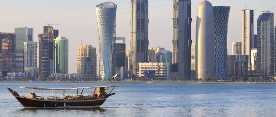 The Doha Corniche skyline in the afternoon across the water with a Dhow in the foreground