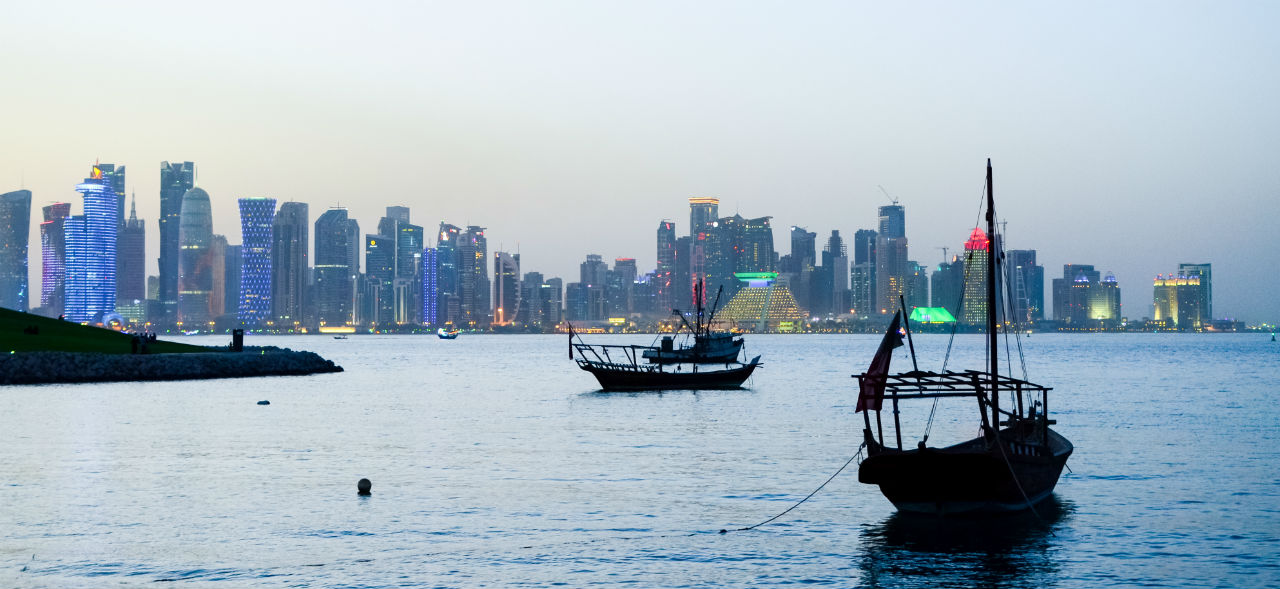Image of dhows in Doha against a backrop of the skyline.