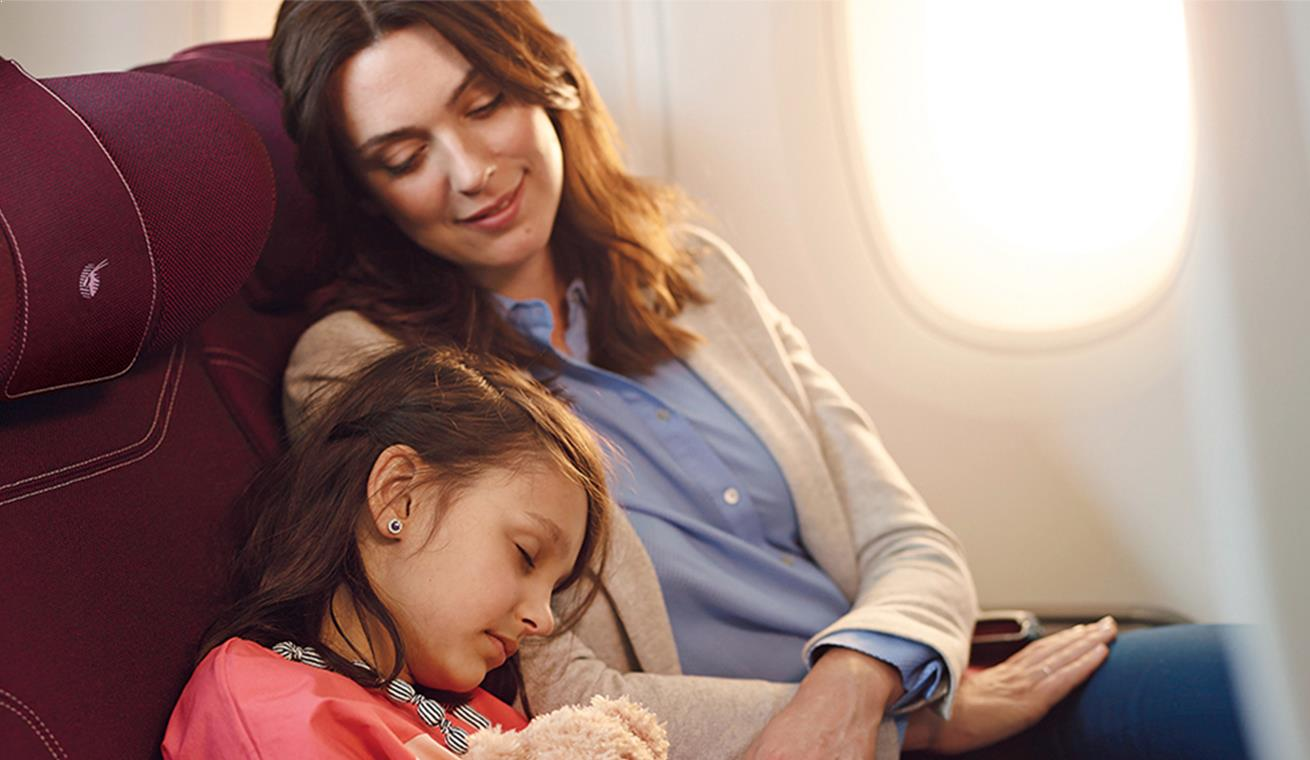 Image of a mother and her daughter sleeping in Qatar Airways Airbus 350 economy class