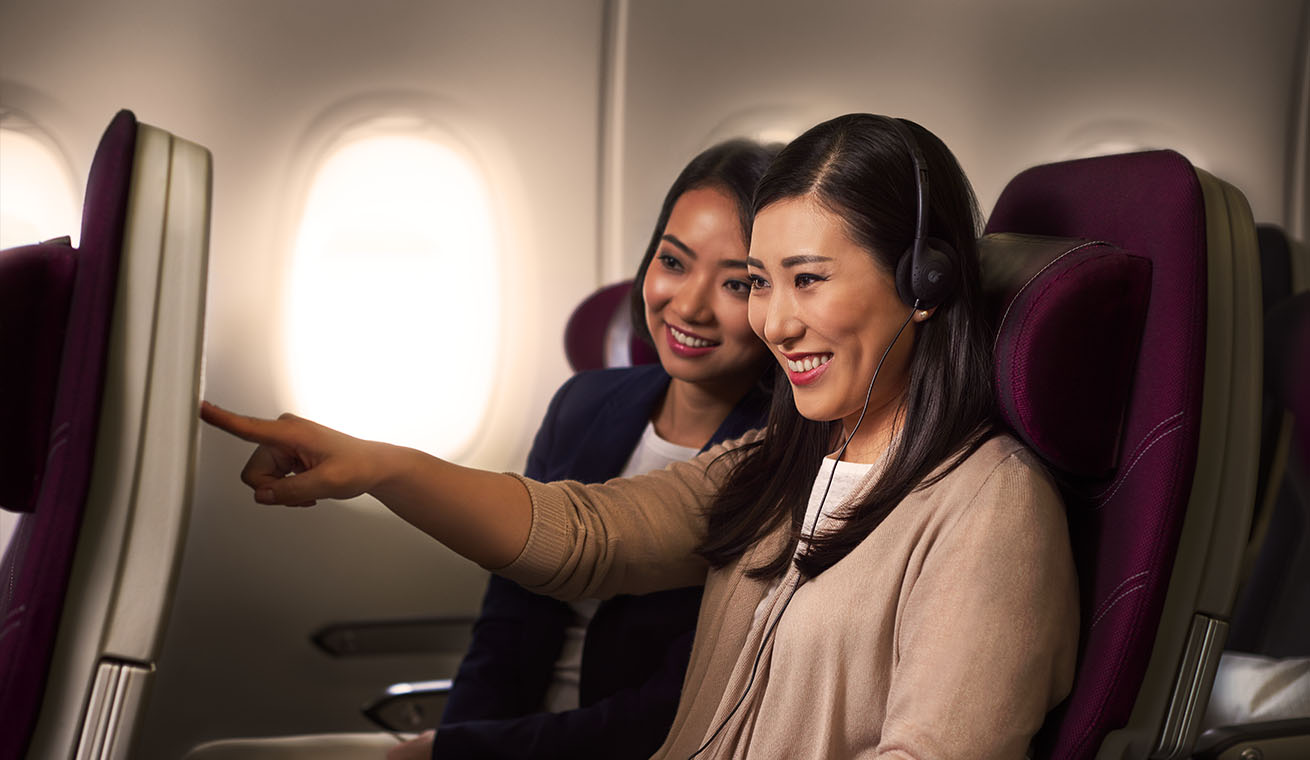 Image of tow ladies using Qatar Airways Airbus 380 In-Flight entertainment happily