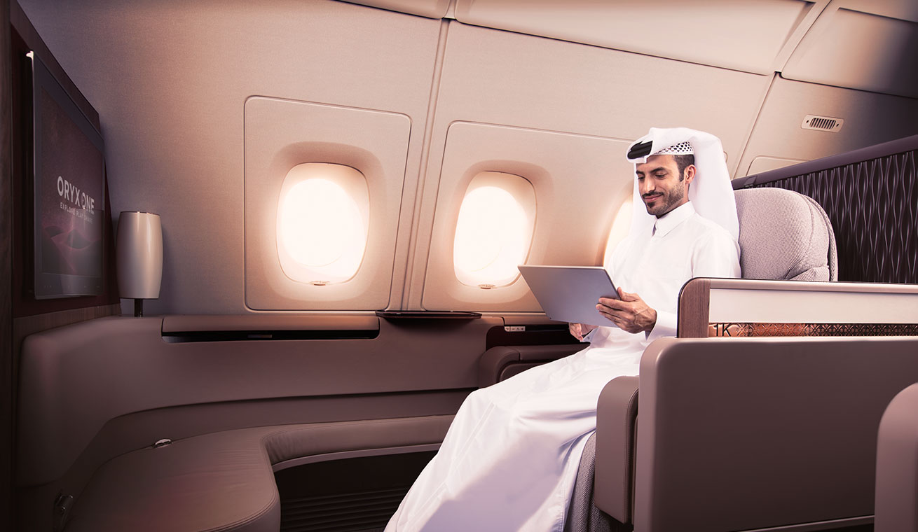 Image of a man dressed in the Qatari national dress using an iPad on board the First Class cabin in the A380 aircraft