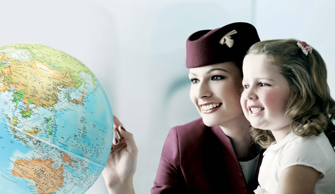 Image of a cabin crew pointing on a globe with a girl