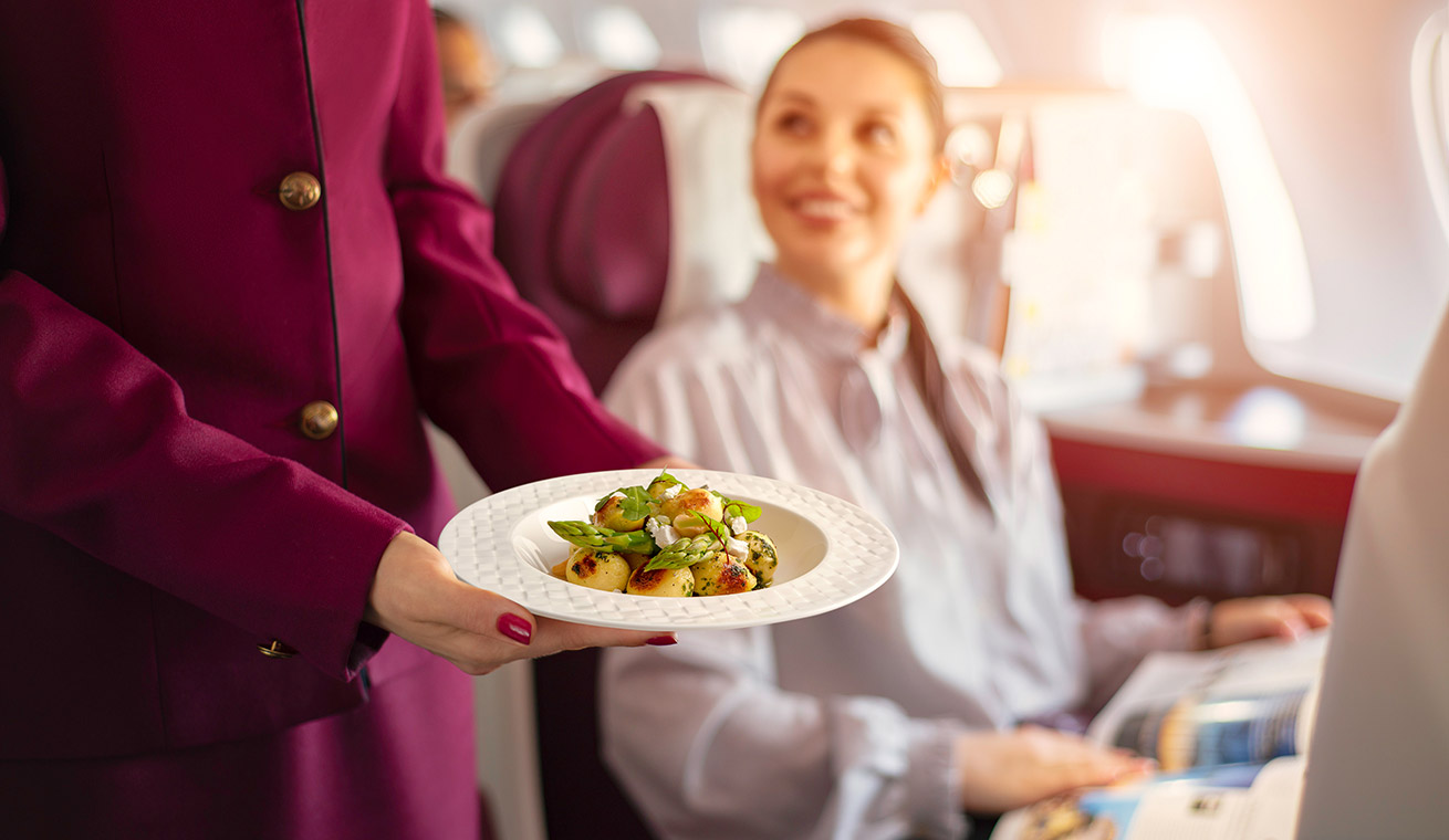 Image of a sample gourmet dish held by a cabin crew on board