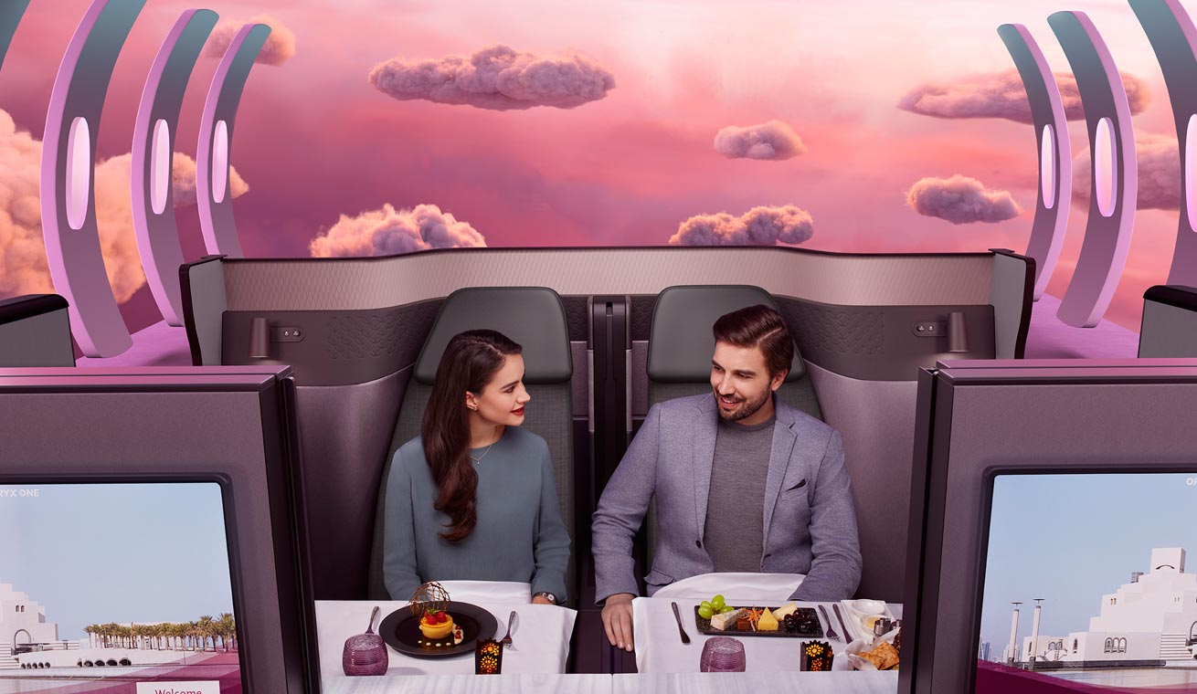 Image of a European couple in a Qsuite cabin being served with a fine-dining cuisine.