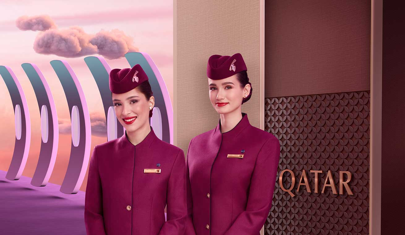 Image of two cabin crews greeting passengers at the Qsuite entrance area.