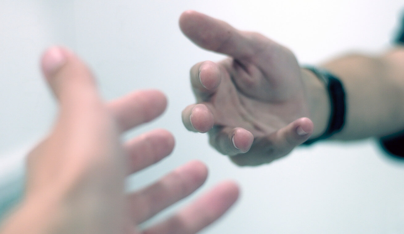 Image of two hands stretching towards each other