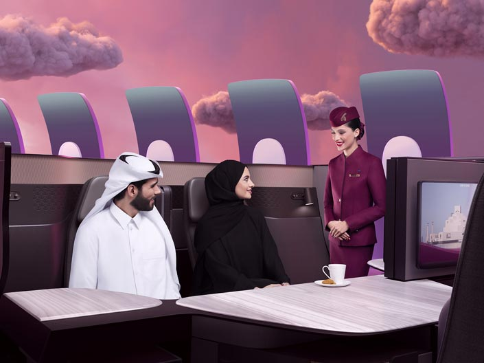 Image of a cabin crew serving a Qatari couple in a Qsuite cabin..