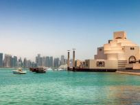 An image of dhows (fishing boats) cruising on the waterfront surrounding the Museum of Islamic Art in Doha, Qatar.