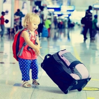 Image of a child pulling a small suitcase at the airport terminal